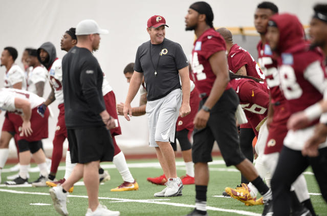 In this June 13, 2018, photo, Washington Redskins coach Jay Gruden, center, smiles during NFL football team practice in Ashburn, Va. Gruden is entering his fifth year as the team's coach. (AP Photo/Nick Wass)