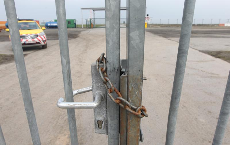 A gate is locked by a chain near to where men made a whole in a fence next to the tarmac at Brussels international airport, Tuesday, Feb. 19, 2013. Police on Tuesday are looking for eight men who made a hole in a security fence of Brussels' international airport, drove onto the tarmac and robbed tens of millions of dollars worth of diamonds from the hold of a Swiss-bound plane. (AP Photo/Yves Logghe)
