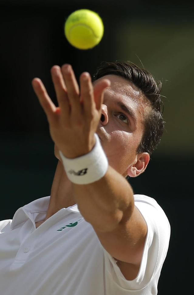 Milos Raonic of Canada serves to Roger Federer of Switzerland during their men's singles semifinal match at the All England Lawn Tennis Championships in Wimbledon, London, Friday, July 4, 2014. (AP Photo/Pavel Golovkin)