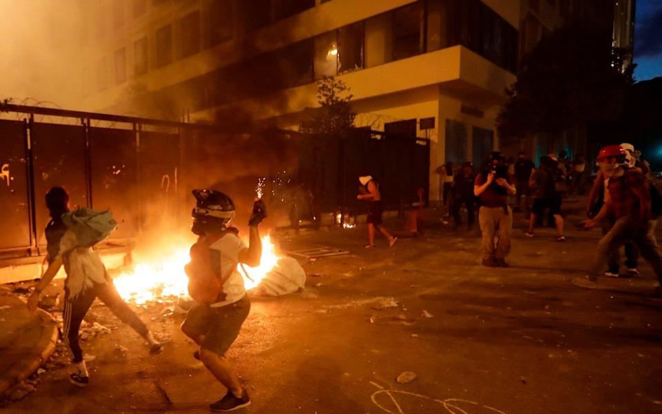 Lebanese protesters, enraged by a deadly explosion blamed on government negligence, clash with security forces for the second evening near an access street to the parliament in central Beirut - AFP