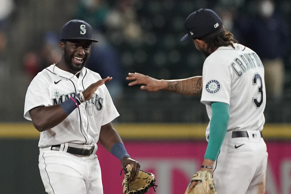 Seattle Mariners center fielder Taylor Trammell, left, greets shortstop J.P. Crawford (3) after the Mariners beat the Los Angeles Dodgers 4-3 in a baseball game, Monday, April 19, 2021, in Seattle. (AP Photo/Ted S. Warren)