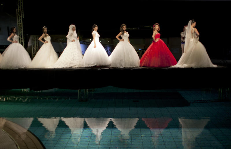 In this photo taken Friday, May 2, 2014, models display creations by designer Fayzeh Pearl on the catwalk during a fashion show on the second day of Palestine Fashion Week 2014, in the West Bank city of Ramallah. (AP Photo/Nasser Nasser)