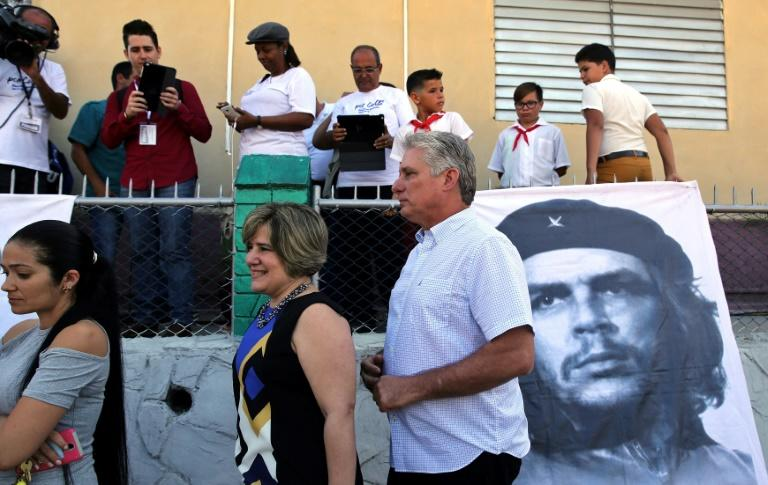 Cubans, including First Vice President Miguel Diaz-Canel (R) and his wife Lis Cuesta (L) stand in line to vote on a new National Assembly that will choose the country's next president