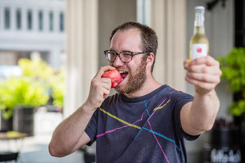 """Jozef Czarnocki bites an apple while holding a bottle of Polish cider to show his support for the twitter action """"#eatapples to spite Putin"""", in Warsaw on July 31, 2014"""