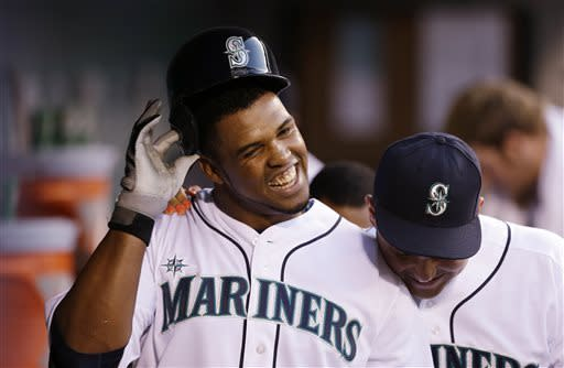 Seattle Mariners' Carlos Peguero, left, is congratulated by Jesus Montero after Peguero's home run against the Los Angeles Angels in the third inning of a baseball game, Thursday, April 25, 2013, in Seattle. (AP Photo/Elaine Thompson)