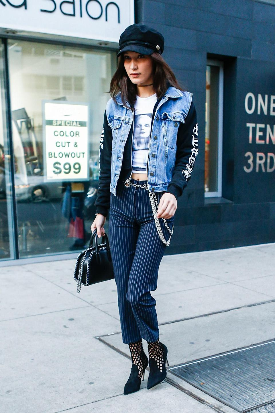 """<p>Gigi's younger sister Bella was also spotted in the brand in early January. She paired the label's <a rel=""""nofollow noopener"""" href=""""https://miaouxx.com/collections/denim/products/brigitte-jean-pinstripe"""" target=""""_blank"""" data-ylk=""""slk:$325 pinstripe pants"""" class=""""link rapid-noclick-resp"""">$325 pinstripe pants</a> with a graphic tee, a hoodie, and a denim vest. She also added the Miaou's $85 <a rel=""""nofollow noopener"""" href=""""https://miaouxx.com/collections/belts/products/chain-belt"""" target=""""_blank"""" data-ylk=""""slk:metal chain-link belt"""" class=""""link rapid-noclick-resp"""">metal chain-link belt </a>and $325 <a rel=""""nofollow noopener"""" href=""""https://miaouxx.com/collections/belts/products/side-piece"""" target=""""_blank"""" data-ylk=""""slk:side piece"""" class=""""link rapid-noclick-resp"""">side piece</a> to the look. (Photo: AKM-GSI) <br><br></p>"""