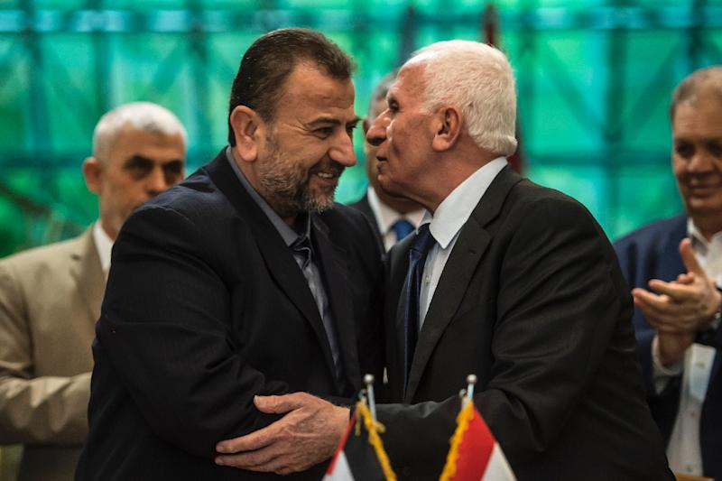 Saleh al-Aruri of Hamas (L) and Fatah's Azzam al-Ahmad (R) kiss after signing a reconciliation deal in Cairo on October 12, 2017