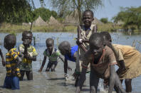 Children wash themselves in muddy floodwaters in the village of Wang Chot, Old Fangak county, Jonglei state, South Sudan Thursday, Nov. 26, 2020. One county in South Sudan is likely in famine and tens of thousands of people in five other counties are on the brink of starvation, according to a new report released Friday, Dec. 11, 2020 by international food security experts. (AP Photo/Maura Ajak)