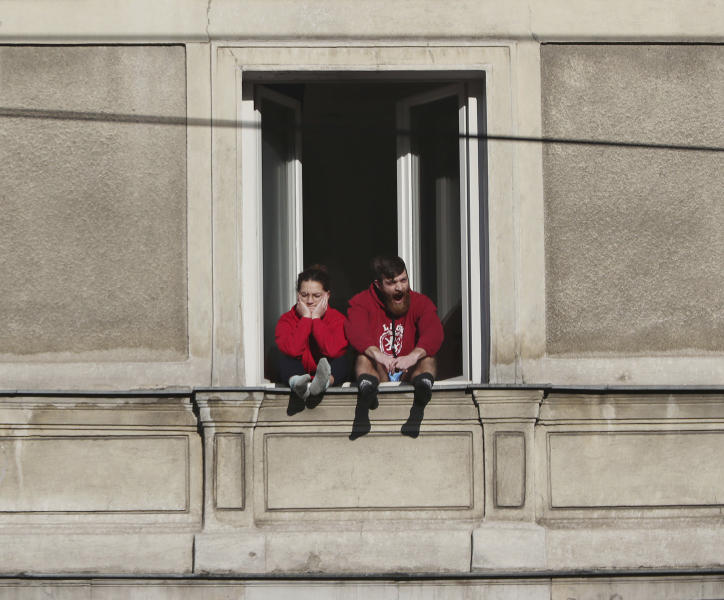 A couple bored with the government-required national isolation at home due to the spreading coronavirus, sits in the 5th floor apartment window on a sunny spring day in downtown Warsaw, Poland, Sunday, March 22, 2020.  For many people the COVID-19 coronavirus causes mild or moderate symptoms, but for some it can cause severe illness. (AP Photo/Czarek Sokolowski)