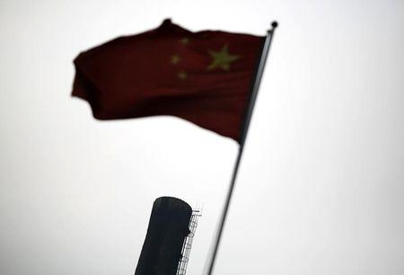 A Chinese national flag is seen in front of the chimney of a heat supply plant in Beijing