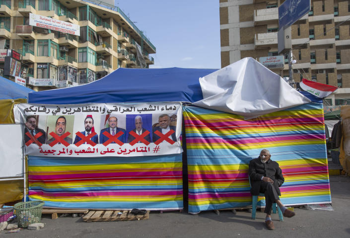 "A protester sits next to a poster with defaced pictures of Iraqi politicians and Arabic that reads, ""the blood of the protesters and the Iraqi people is on your necks, the conspirators on the people and the religious authority,"" during ongoing protests, in Tahrir square, in Baghdad, Iraq, Wednesday, Dec. 25, 2019. (AP Photo/Nasser Nasser)"