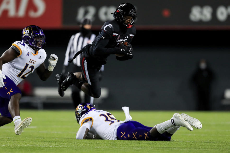 East Carolina linebacker Xavier Smith, left, defends as Cincinnati wide receiver Jordan Jones, middle, jumps over East Carolina defensive back Jireh Wilson during the first half of an NCAA college football game, Friday, Nov. 13, 2020, in Cincinnati. (AP Photo/Aaron Doster)