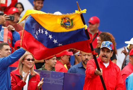 Venezuela's President Nicolas Maduro waives a Venezuelan flag next to his wife Cilia Flores during a rally in support of the government and to commemorate the 20th anniversary of the arrival to the presidency of the late President Hugo Chavez in Caracas, Venezuela February 2, 2019. REUTERS/Manaure Quintero