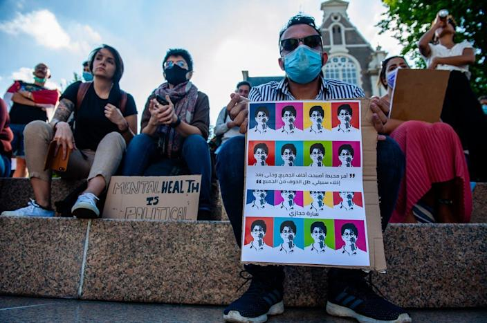 """<span class=""""caption"""">A memorial to Egyptian activist Sarah Hegazi in Amsterdam, June 19, 2020. </span> <span class=""""attribution""""><a class=""""link rapid-noclick-resp"""" href=""""https://www.gettyimages.com/detail/news-photo/man-wearing-a-mouth-mask-is-holding-a-placard-with-the-news-photo/1221109194?adppopup=true"""" rel=""""nofollow noopener"""" target=""""_blank"""" data-ylk=""""slk:Romy Arroyo Fernandez/NurPhoto via Getty Images"""">Romy Arroyo Fernandez/NurPhoto via Getty Images</a></span>"""