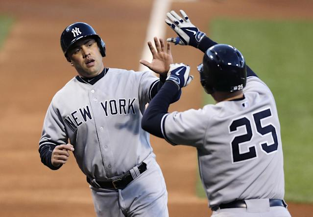 New York Yankees' Carlos Beltran, left, is congratulated by teammate Mark Teixeira (25) after scoring on a double hit by Alfonso Soriano during the first inning of a baseball game against the Boston Red Sox, Thursday, April 24, 2014, in Boston. (AP Photo/Charles Krupa)