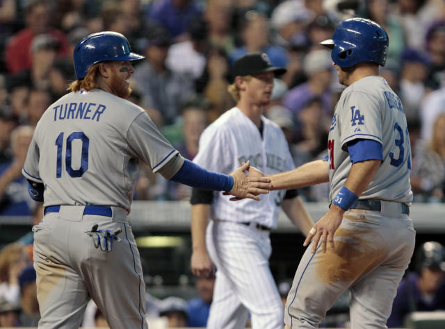 Los Angeles Dodgers' Justin Turner (10) congratulates Dodgers' Drew Butera (31) after they scored in the sixth inning of a baseball game on Dodgers batter Dee Gordon's single off Colorado Rockies pitcher Eddie Butler, center, in Denver on Friday, June 6, 2014. (AP Photo/Joe Mahoney)
