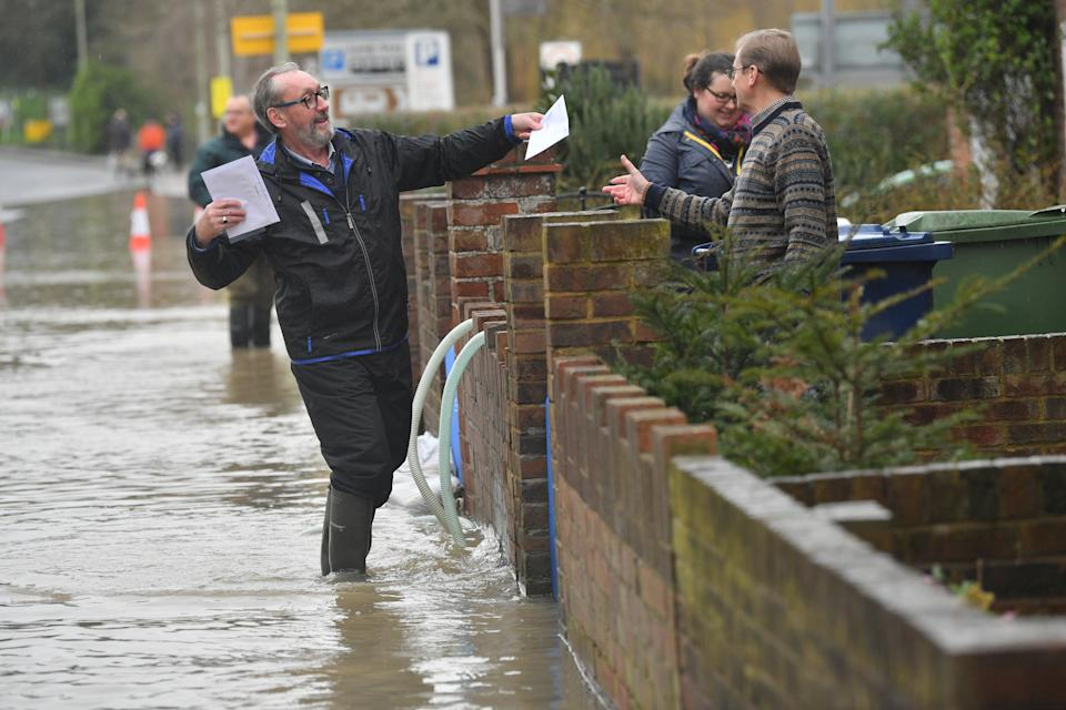 A man helping a postman deliver letters to residents in Gloucester Road in Tewkesbury, Gloucestershire, following the aftermath of Storm Dennis.