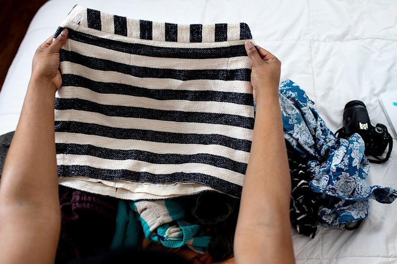A woman looks at a skirt to decide if she wants to sell it online.