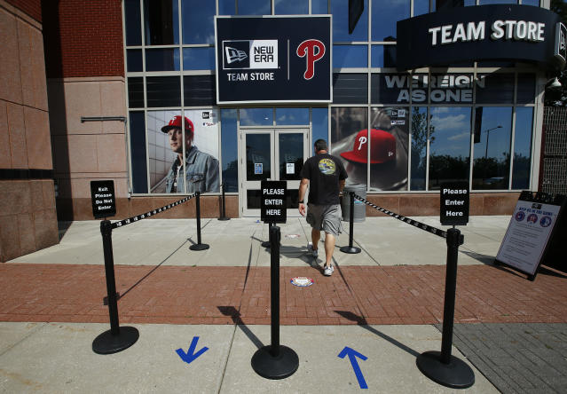 A person walks toward the Philadelphia Phillies team store at Citizens Bank Park on Monday, July 27, 2020, in Philadelphia. The Phillies' game against the New York Yankees on Monday was postponed after several members of the Miami Marlins tested positive for the coronavirus. (Yong Kim/The Philadelphia Inquirer via AP)