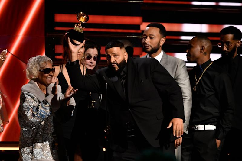 DJ Khaled (center) and John Legend (right) accept the award for best rap/sung performance and honor their late collaborator Nipsey Hussle at the Grammy Awards.
