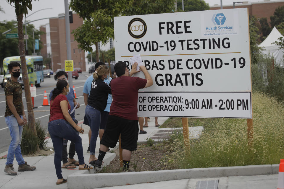 People fill out forms at a mobile Coronavirus testing site at the Charles Drew University of Medicine and Science Wednesday, July 22, 2020, in Los Angeles. California's confirmed coronavirus cases have topped 409,000, surpassing New York for most in the nation. (AP Photo/Marcio Jose Sanchez)