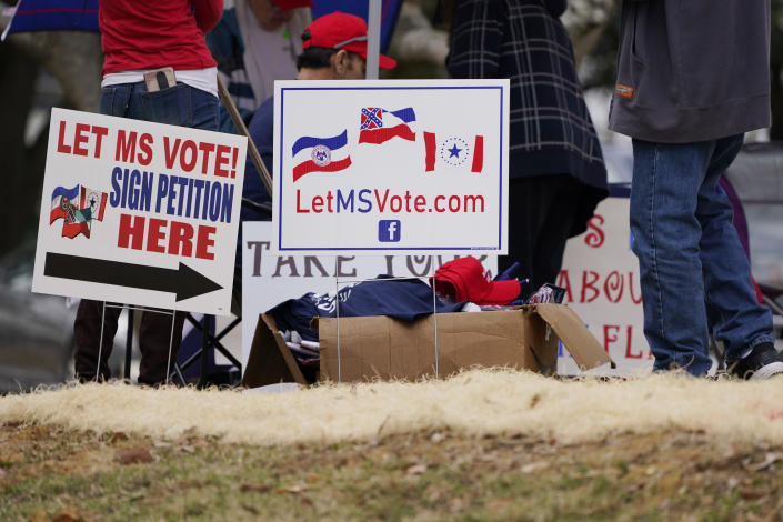 Signage calling for a revote on the new state flag was prominently displayed at a pro-Trump protest of the constitutional process to affirm the president-elect's victory in the November election at the Capitol in Jackson, Miss., Wednesday, Jan. 5, 2021. The small group of protestors called for voters to have a choice of banners but tended to support the retired state flag that incorporated a Confederate battle emblem. (AP Photo/Rogelio V. Solis)