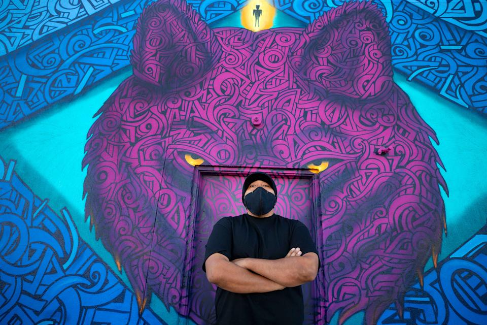 Artist Thomas Breeze Marcus, stands in front of his mural in South Phoenix. Marcus was one of the five lead muralists from Indigenous Peoples of present-day Arizona that participated in creating work related to the election, the future of Indigenous communities, and collective society.