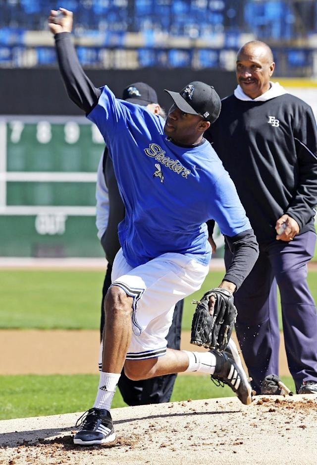 Retired NBA All-Star Tracy McGrady delivers a pitch at the Sugar Land Skeeters baseball stadium as former major league pitcher Scipio Spinks, right, stands near Wednesday, Feb. 12, 2014, in Sugar Land, Texas. McGrady hopes to tryout for the independent Atlantic League Skeeters. (AP Photo/Pat Sullivan)