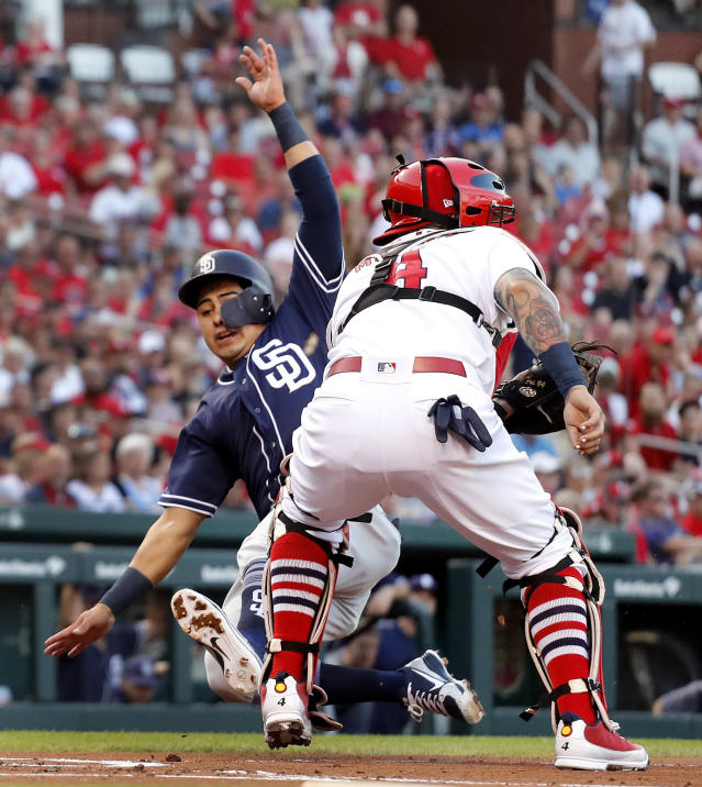 San Diego Padres' Christian Villanueva, left, scores past St. Louis Cardinals catcher Yadier Molina during the first inning of a baseball game Wednesday, June 13, 2018, in St. Louis. (AP Photo/Jeff Roberson)