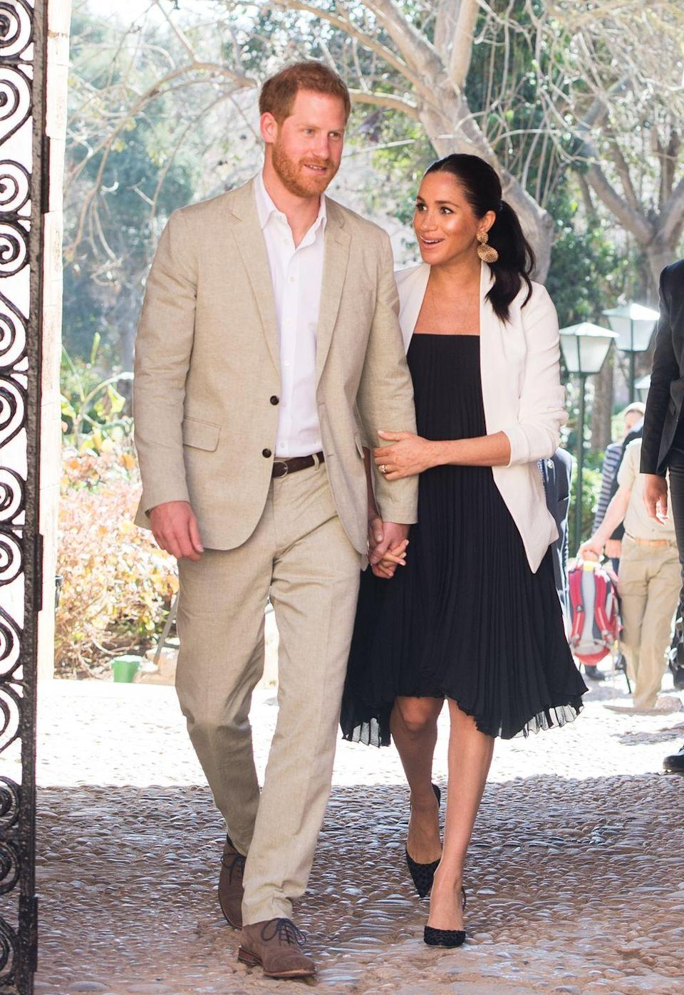 <p>Harry and Meghan walked through the Andalusian Gardens in Rabat holding hands, with Meghan also holding onto her husband's arm. </p>