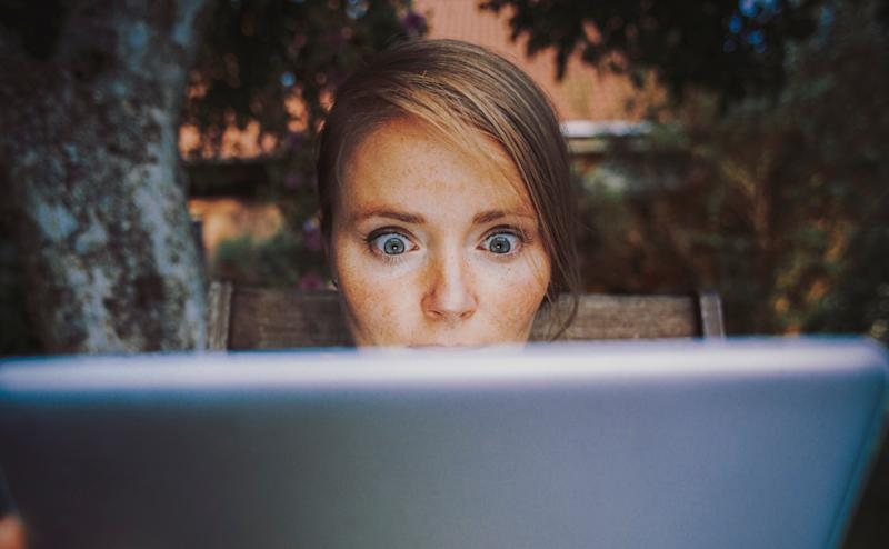A woman looking shocked while staring at a computer screen.