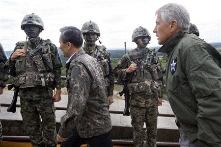 U.S. Secretary of Defense Hagel walks past South Korean soldiers with South Korea's Defence Minister Kim during a tour of the DMZ in Panmunjom
