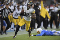 Pittsburgh Steelers running back James Conner, left, gets by Los Angeles Chargers outside linebacker Jatavis Brown as he runs for a touchdown during the first half of an NFL football game, Sunday, Oct. 13, 2019, in Carson, Calif. (AP Photo/Kyusung Gong)