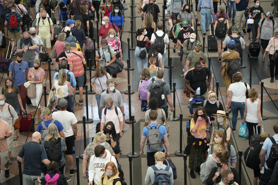 Travelers queue up in long lines to pass through the south security checkpoint in Denver International Airport, Wednesday morning, June 16, 2021, in Denver. (AP Photo/David Zalubowski)