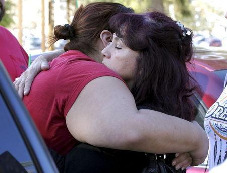Teresa Hernandez (R) hugs Monique Gutierrez at the Rudy Hernandez Community Center as they wait for a relative who was not injured after a shooting rampage at the Inland Regional Center in San Bernardino, December 2, 2015. REUTERS/Alex Gallardo
