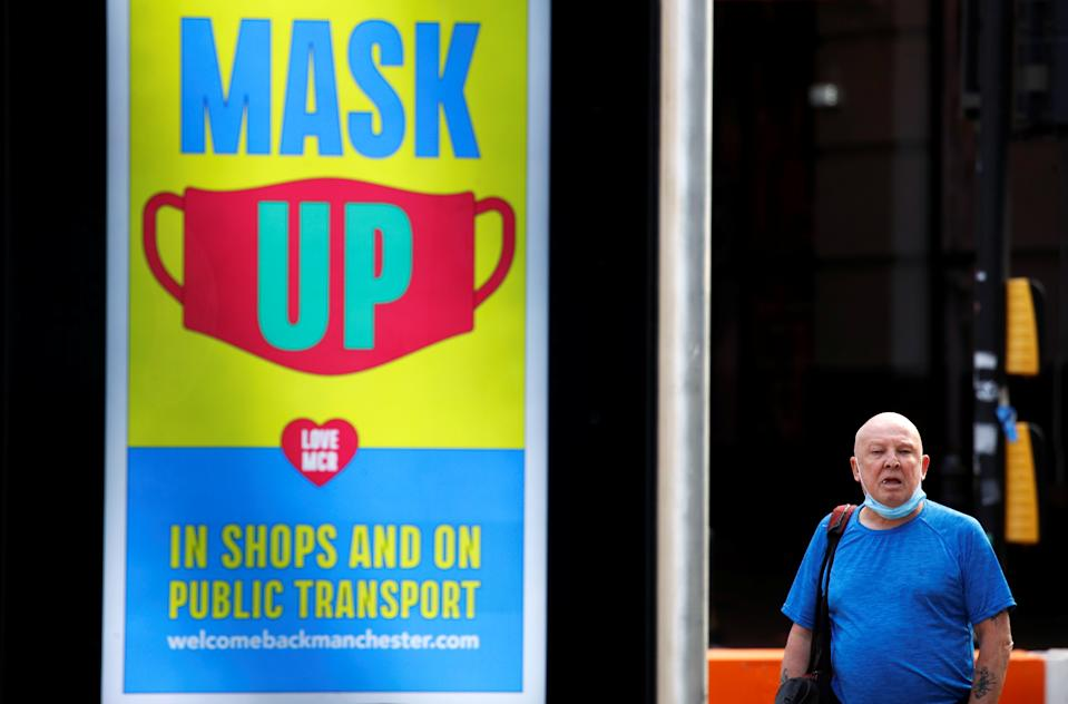 A man stands next to a sign promoting the use of protective face mask in Manchester, as the city and surrounding areas face local restrictions in an effort to avoid a local lockdown being forced upon the region, amid the coronavirus disease (COVID-19) outbreak, in Manchester, Britain August 3, 2020. REUTERS/Phil Noble