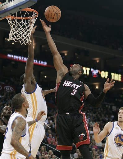 Miami Heat's Dwyane Wade (3) lays up a shot against the Golden State Warriors during the first half of an NBA basketball game Tuesday, Jan. 10, 2012, in Oakland, Calif. (AP Photo/Ben Margot)