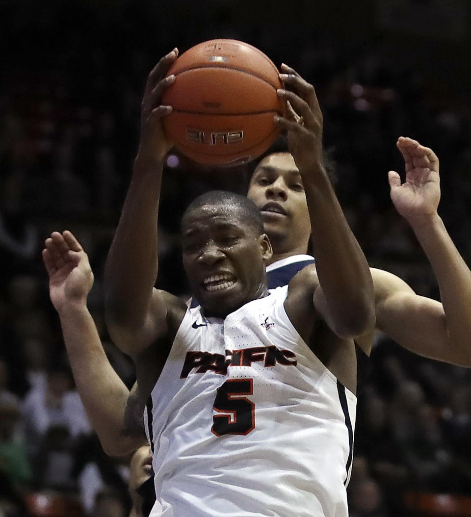 Pacific's Anthony Townes (5) pulls in a rebound in front of Gonzaga's Brandon Clarke during the first half of an NCAA college basketball game Thursday, Feb. 28, 2019, in Stockton, Calif. (AP Photo/Ben Margot)