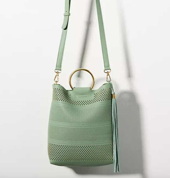 Perforated crossbody Bag with gold Ring Handle in green. Image via Anthropologie.