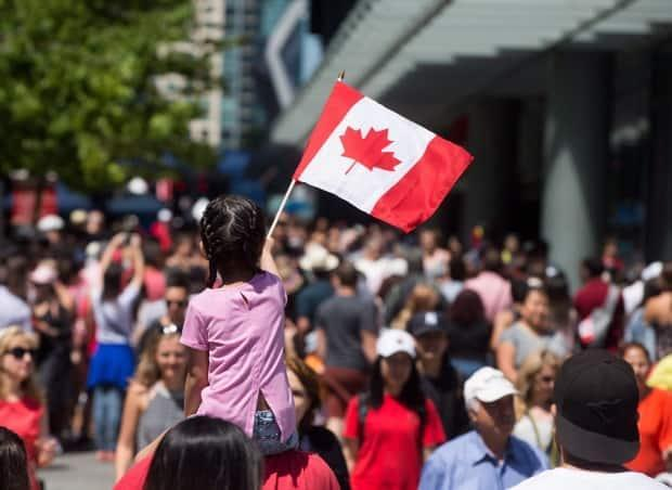 A young girl waves a Canadian flag while being carried through the crowd during Canada Day celebrations in Vancouver, B.C., on Saturday, July 1, 2017. (Darryl Dyck/Canadian Press - image credit)