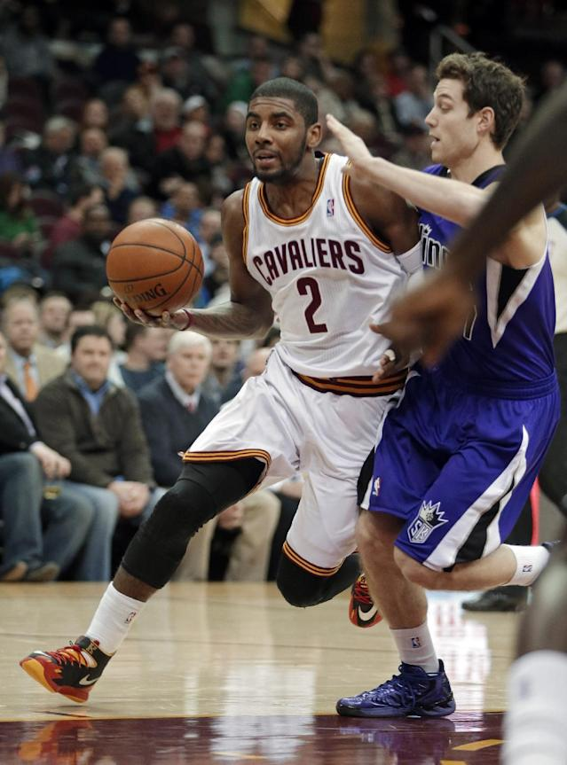 Cleveland Cavaliers' Kyrie Irving (2) drives past Sacramento Kings' Jimmer Fredette during the first quarter of an NBA basketball game Tuesday, Feb. 11, 2014, in Cleveland. (AP Photo/Mark Duncan)