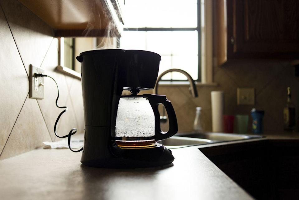 "<p>While you should be washing all removable parts of your coffee maker with dish soap after every use, you should also <a href=""https://www.goodhousekeeping.com/home/cleaning/tips/a26565/cleaning-coffee-maker/"" rel=""nofollow noopener"" target=""_blank"" data-ylk=""slk:decalcify your coffee maker every month with vinegar"" class=""link rapid-noclick-resp"">decalcify your coffee maker every month with vinegar</a>, according to <em>Good Housekeeping</em>. To do so, fill the reservoir with equal parts vinegar and water, and place a paper filter into the machine's empty basket. Put your pot in place, ""brew"" the solution halfway, and then turn off the machine. </p><p>After letting it sit for 30 minutes, turn the coffee maker back on, finish the brewing, and dump the full pot of vinegar and water. Rinse everything out by putting in a new paper filter and brewing a full pot of clean water. </p>"