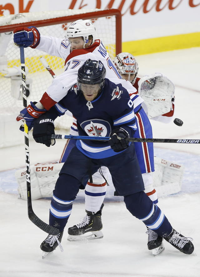 Montreal Canadiens goaltender Carey Price (31) keeps his eyes on the puck as Brett Kulak (17) defends against Winnipeg Jets' Andrew Copp (9) during the first period of an NHL hockey game Saturday, March 30, 2019 in Winnipeg, Manitoba. (John Woods/The Canadian Press via AP)