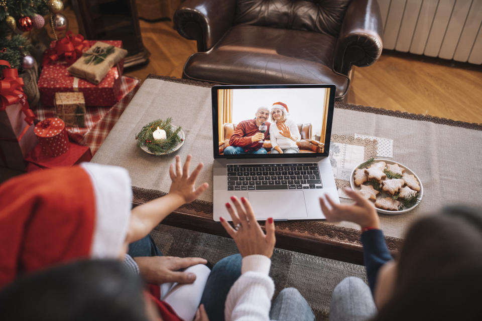 Family and their children wave with hand in video call on Christmas. (Getty Images)