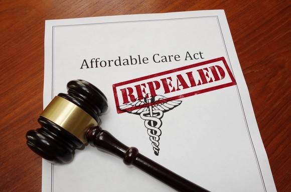 An Affordable Care Act plan, stamped with the word repealed, next to judge's gavel.