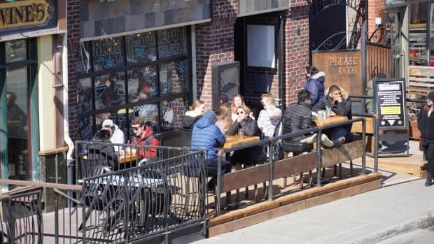 People sit on a patio at a restaurant in the ByWard Market on Friday, April 2, 2021. It was the last day people could dine indoors or outdoors at restaurants across Ontario before the provincewide shutdown came into effect Saturday.