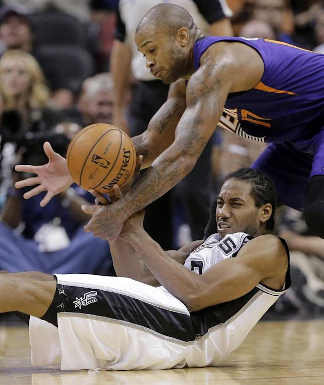 Phoenix Suns' P.J. Tucker, top, and San Antonio Spurs' Kawhi Leonard battle for a loose ball during the second half of an NBA basketball game Wednesday, Nov. 6, 2013, in San Antonio. (AP Photo/Eric Gay)