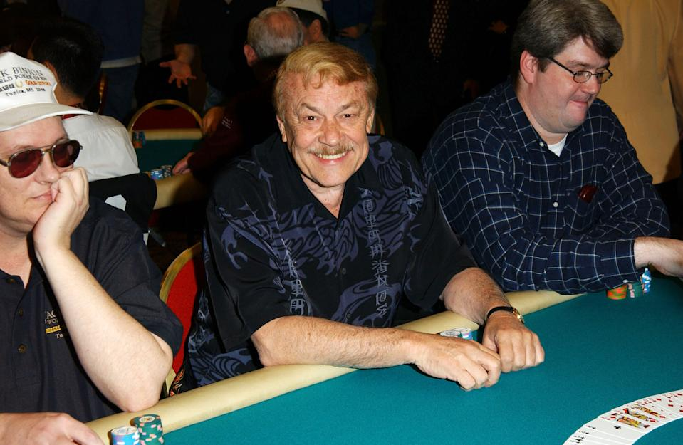 """Los Angeles Lakers owner Dr. Jerry Buss (C) plays poker during the """"Celebrities and Pros Match Skills As World Poker Tour Hits Los Angeles"""" at the Commerce Casino on February 25, 2003 in Commerce, California. (Photo by Jon Kopaloff/Getty Images)"""