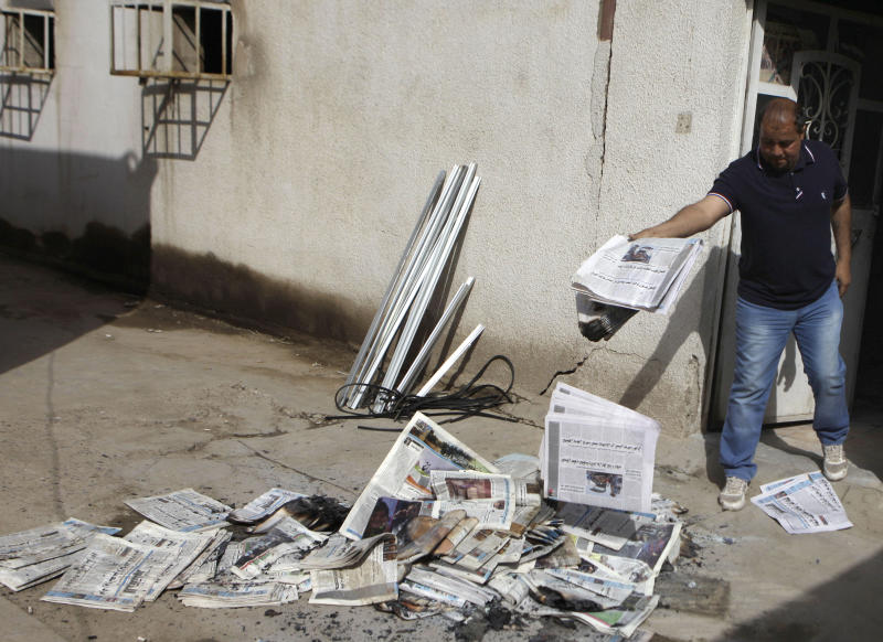 A man cleans up the offices of the Iraqi newspaper, the Constitution, in Baghdad, Iraq, Tuesday, April 2, 2013. Iraqi officials say on Monday, April 1, 2013 gunmen, some wearing military uniforms, broke into the offices of four independent newspapers in Baghdad and stabbed and beat five employees there also damaged computers and office furniture. (AP Photo/ Khalid Mohammed)