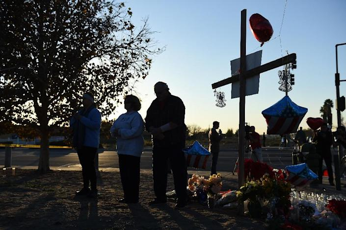 People pray December 4, 2015 at a makeshift memorial near the Inland Regional Center in San Bernardino, California after 14 were killed December 2 in a mass shooting there (AFP Photo/Robyn Beck)